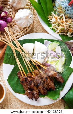 Satay or sate, skewered and grilled meat, served with peanut sauce, cucumber and ketupat. Traditional Malaysian food. Delicious hot and spicy Malay dish, Asian cuisine. - stock photo