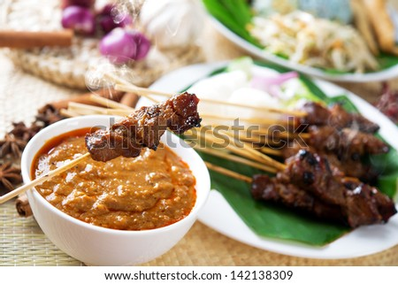 Satay or sate, skewered and grilled meat, served with peanut sauce, cucumber and ketupat. Traditional Malay food. Malaysian dish, Asian cuisine. - stock photo