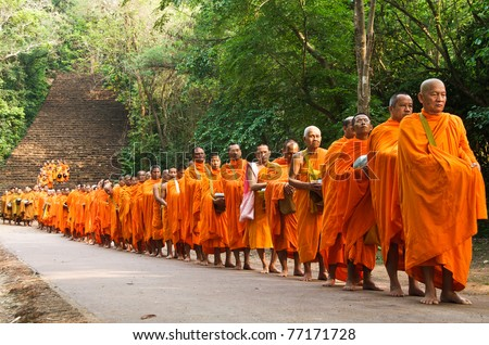 Satchanalai District. Sukhothai, THAILAND - APRIL 13: Thai people celebrate Songkran festival (water festival) in Satchanalai District. Sukhothai, Thailand on April 13, 2011. Row of Buddhist monks. - stock photo