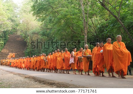 Satchanalai District. Sukhothai, THAILAND - APRIL 13: Thai people celebrate Songkran festival (water festival) in Satchanalai District. Sukhothai, Thailand on April 13, 2011. Row of Buddhist monks.