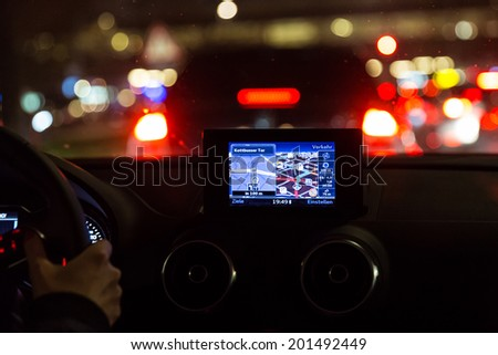 Satelite navigation device in a car at night - stock photo