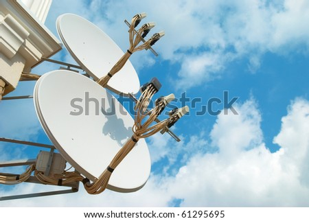 Satellite antenna on the wall with blue sky - stock photo