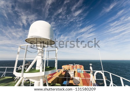 Satellite communication antenna on the top of large container ship - stock photo