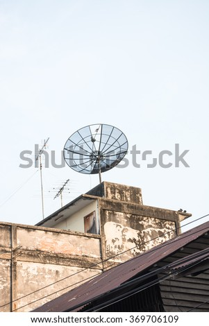 Satellite damaged and antenna on the old building. - stock photo