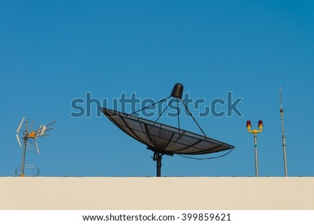 Satellite dish and lightning rod on the building against blue sky
