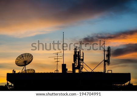 Satellite dish and Telecoms tower in twilight at sunset. - stock photo