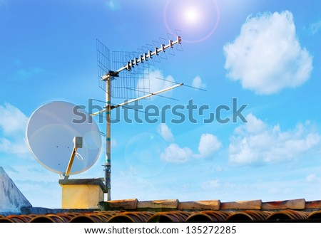 satellite dish and tv antenna on a sunny day - stock photo