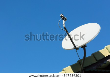 satellite dish and TV antennas on the house roof with blue sky background - stock photo