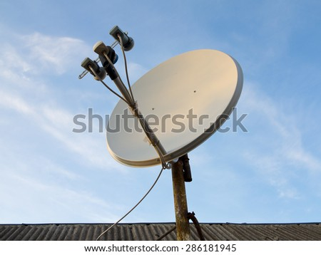 Satellite dish antenna over blue sky and roof background  - stock photo
