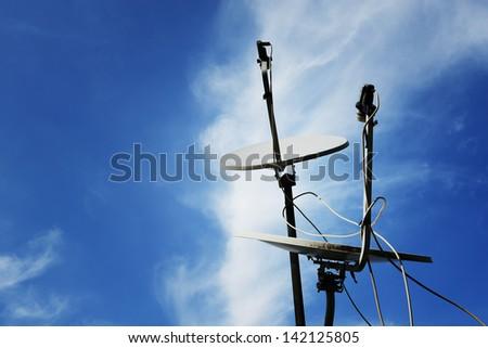 Satellite dish antenna over blue sky background - stock photo