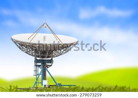 satellite dish antenna radar big size and blue sky grass background - stock photo