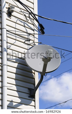 Satellite dish on a wall of a typical American house - stock photo