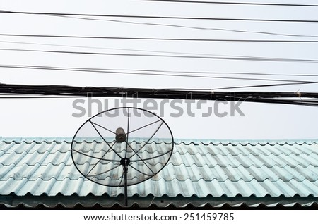 Satellite dish on roof against telephone line / Satellite dish - stock photo