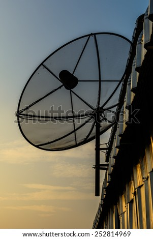Satellite dish on roof in sunset
