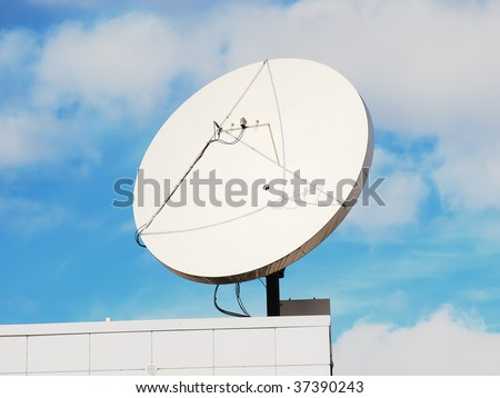 Satellite dish on the modern building roof corner with blue sky in the background. - stock photo