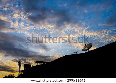 Satellite dish on the roof and evening sky - stock photo