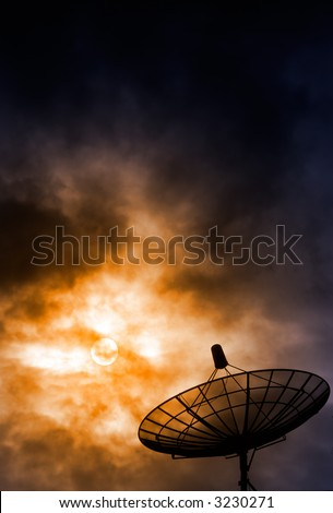 Satellite Dish on the roof in the foreground with sun shining through clouds in the background.