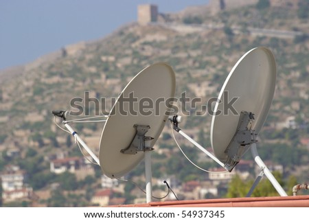 Satellite dish on the roof of a house with clipping paths - stock photo