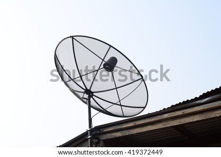 Satellite dish on top roof of wooden house, communication technology network