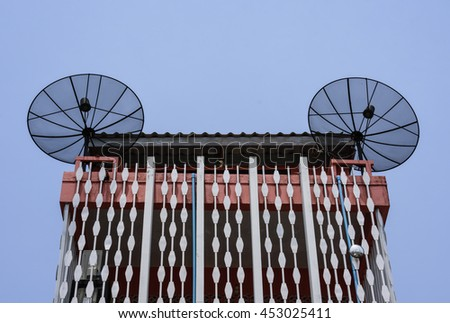 Satellite dish, satellite antenna mounted on the roof of a house with a beautiful pattern. - stock photo