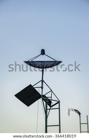 Satellite dish transmission data on colorful sky background - stock photo