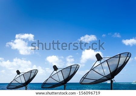 Satellite dish with ocean background - stock photo