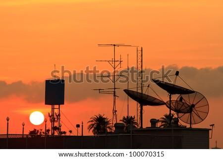 satellite dishes over sunset - stock photo