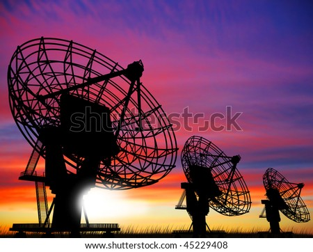satellite dishes over sunset - stock photo
