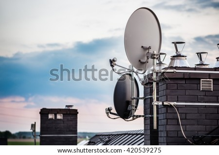 Satellite dishes, satellite antennas mounted on the chimney of a new home. Evening