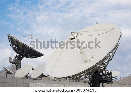 Satellite dishes used in telecommunication, against the sky - stock photo