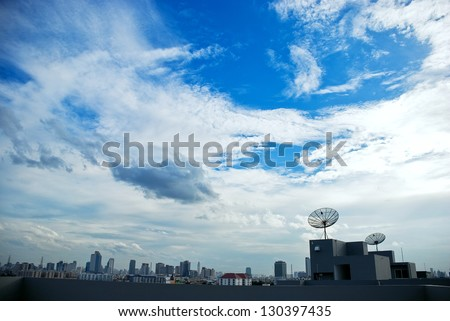 Satellite on rooftop with blue sky - stock photo