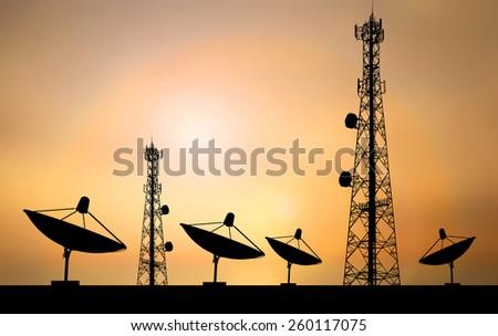 Satellite shadow and phone antenna orange sky background - stock photo
