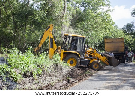 Sathyamangalam, Tamil Nadu, India - June 24, 2015: An excavator doing roadwork in the middle of the Sathyamangalam forest. - stock photo