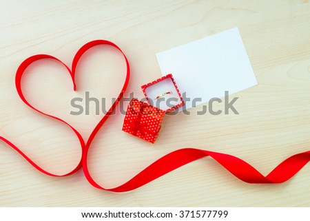 Satin ribbon with heart-shaped box for an engagement ring on Valentine's Day