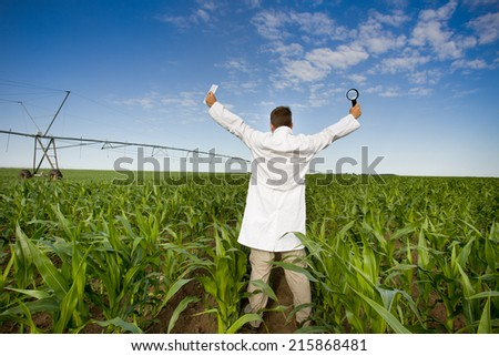 Satisfied agronomist in white coat standing in corn field with spread hands - stock photo