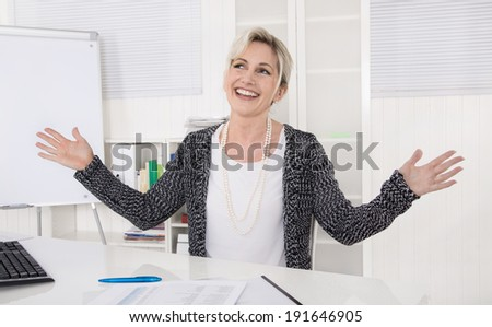 Satisfied and cheering business woman sitting at desk. - stock photo