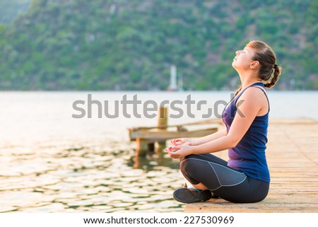 satisfied athlete relaxes on a pier in the morning - stock photo