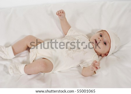 satisfied baby lying on a bed in the white hat - stock photo