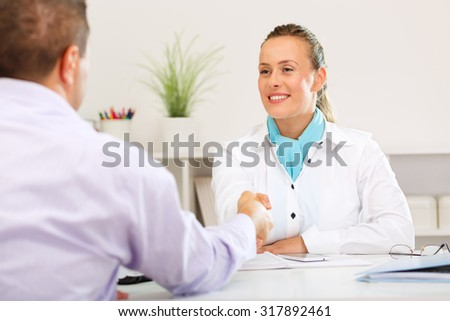 Satisfied bank clerk and client shake hands after successful meeting. - stock photo