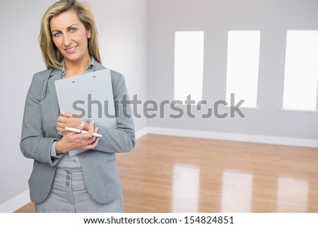 Satisfied blonde realtor standing in an empty room holding documents - stock photo