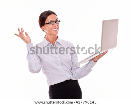 Satisfied brunette businesswoman holding a laptop with a toothy smile while looking at the camera and wearing her straight hair back with a button down shirt making a gesture with one hand, isolated - stock photo