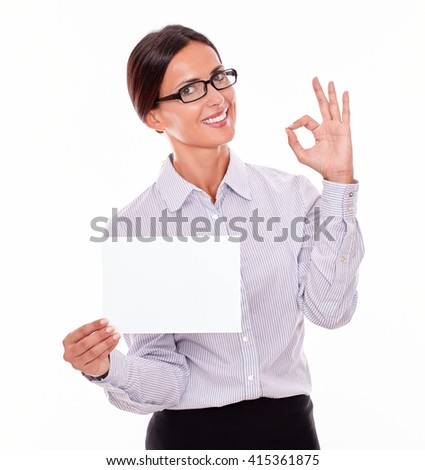 Satisfied brunette businesswoman with glasses, wearing her long hair tied back, and a button down shirt, holding a blank copy space in one hand, gesturing perfect with the other hand
