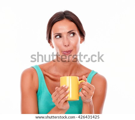 Satisfied brunette woman with coffee mug looking away, licking her lips while wearing a green tank top and her long hair tied back isolated - stock photo