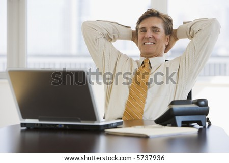 Satisfied business executive sitting back in his chair - stock photo