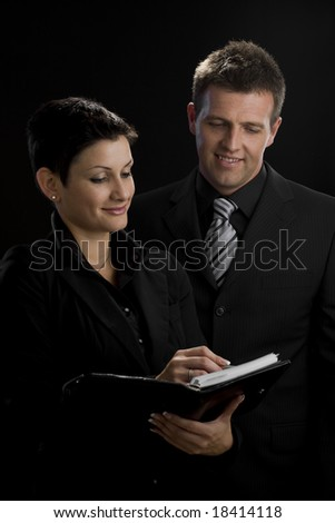 Satisfied business executives looking at notebook working together.
