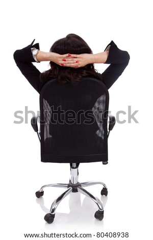 Satisfied business woman with hands crossed behind her head - stock photo