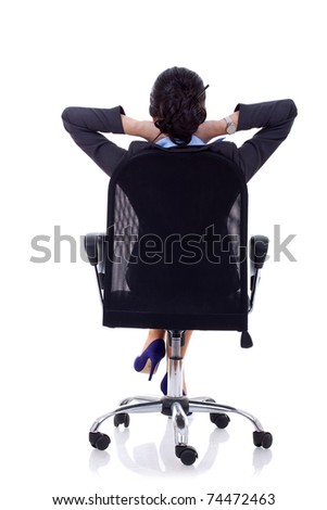 Satisfied business woman with hands crossed behind her head - back picture - stock photo