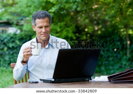 Satisfied businessman relaxing outdoor while drinking a mug of coffee