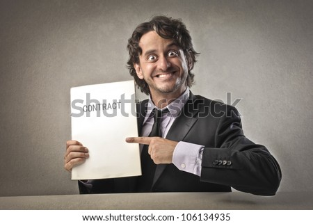 Satisfied businessman showing a contract - stock photo