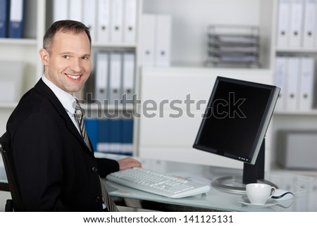 Satisfied businessman sitting in front of his table with computer - stock photo